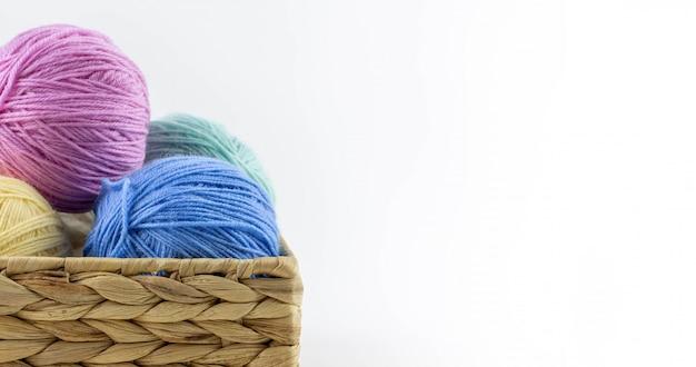 Mehrfarbige garnknäuel zum stricken liegen in einem weidenkorb
