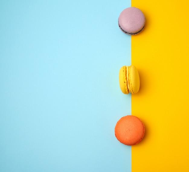 Mehrfarbige gebackene runde macarons auf blau und orange