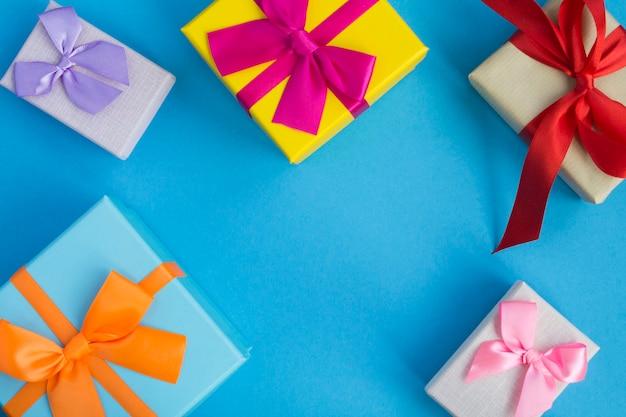 Mehrfarbige geschenkboxen mit hellen schleifen auf der blauen oberfläche. draufsicht. speicherplatz kopieren.