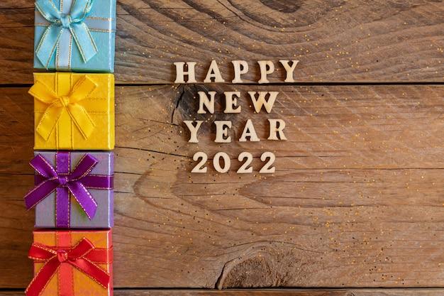 Mehrfarbige geschenkboxen. neujahrsgeschenke auf holztisch. tex frohes neues jahr 2022. festliche grußkarte. flach liegen.