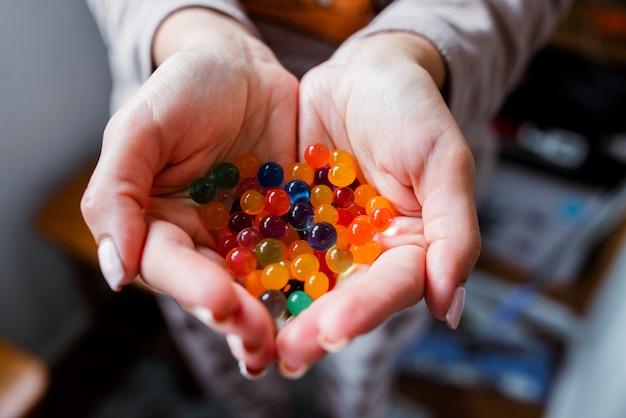 Mehrfarbige glaskugeln in ihren händen.