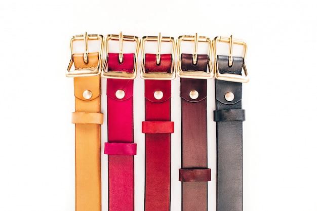 Mehrfarbige gürtel. viele ledergürtel auf weißem hintergrund. rote, gelbe, blaue, braune, grüne gürtel sind auf einem weißen geschnitzt