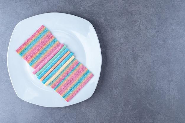 Mehrfarbige gummiartige bonbons auf einem teller auf marmortisch.