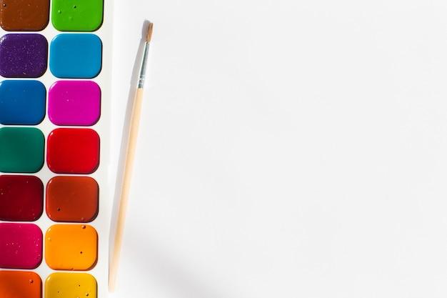 Mehrfarbige helle aquarellfarben mit einem pinsel. ein rahmen von den farben auf einem weißen hintergrund