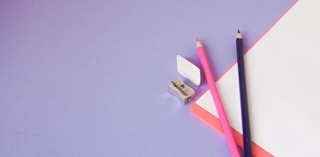 Mehrfarbige, helle, bunte stifte befinden sich unten in einem winkel und ein notizbuch für ihren text auf einem violetten hintergrund.