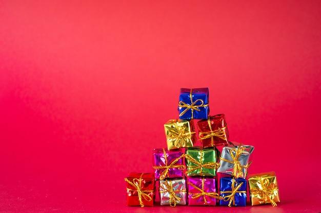 Mehrfarbige helle weihnachtsgeschenkboxen auf rot