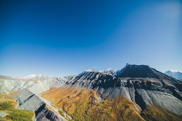 Mehrfarbige herbstlandschaft mit schneebedecktem berggipfel und grauen rockies mit orange und lila tönung. spektakuläre farbenfrohe aussicht auf den scharfen bergrücken im herbst. bunte berglandschaft in herbstlichen farben.