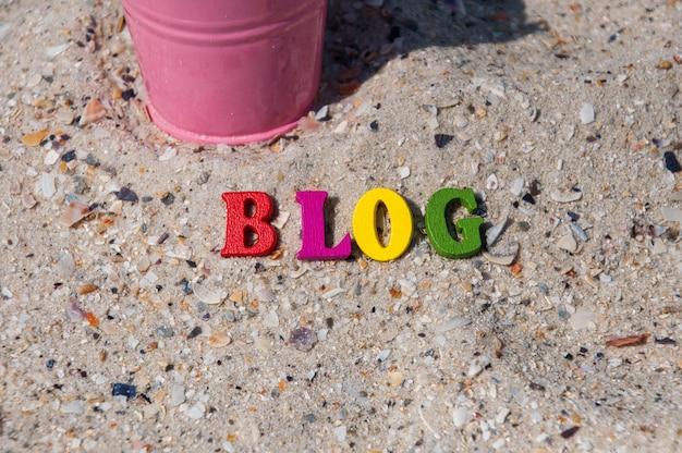Mehrfarbige hölzerne buchstaben auf dem sand