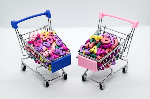 Mehrfarbige hölzerne buchstaben und zahlen in zwei supermarktwagen auf weißem hintergrund. platz für text.
