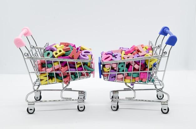 Mehrfarbige hölzerne buchstaben und zahlen in zwei supermarktwagen auf weißer wand. platz für text. vergleich der mathematischen und humanitären denkweise. konzept: zurück in die schule.