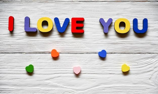 Mehrfarbige holzbuchstaben bilden die inschrift ich liebe dich und mehrfarbige holzherzen auf einem weißen holzhintergrund. hintergrund zum valentinstag.