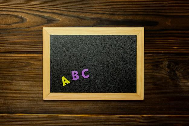 Mehrfarbige holzbuchstaben buchstaben abc an der tafel