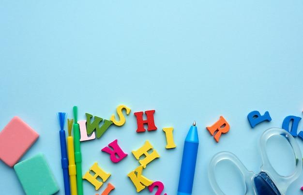 Mehrfarbige holzbuchstaben des englischen alphabets, pinsel, stift und schere auf blauem grund