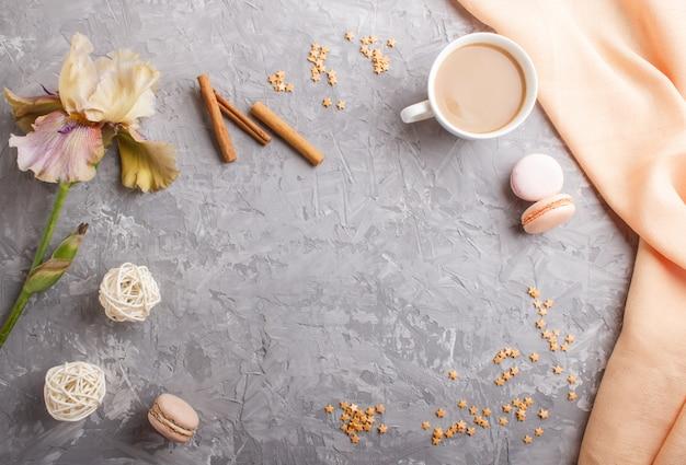Mehrfarbige irisblumen und ein tasse kaffee auf grauem beton
