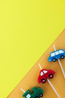 Mehrfarbige kerzenautos auf gelber fläche mit platz für text
