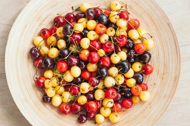 Mehrfarbige kirschen auf schüssel. weiße und rote kirschen. nahaufnahme. saisonale sommerfrüchte. gesundes essen. tiefenschärfe