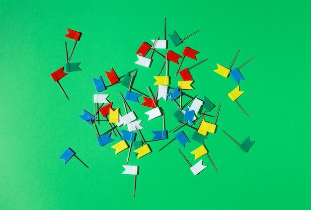 Mehrfarbige kleine flaggenstifte auf grünem hintergrund. sicht von oben .