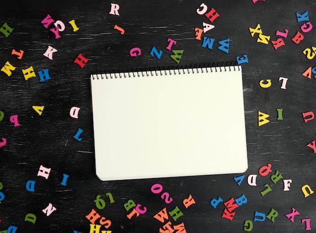 Mehrfarbige kleine hölzerne buchstaben des notizbuches des englischen alphabetes und des papiers