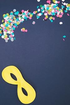 Mehrfarbige konfetti mit gelber augenmaske auf farbigem hintergrund