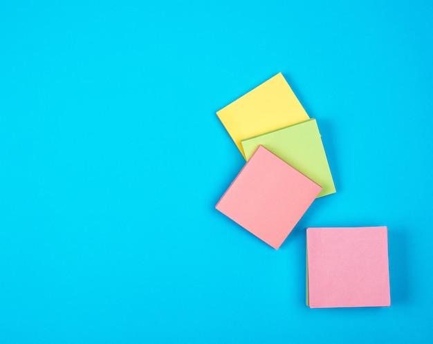 Mehrfarbige leere quadratische papieraufkleber auf blau