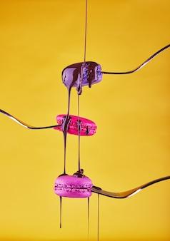 Mehrfarbige macarons auf gabeln mit schokolade von oben