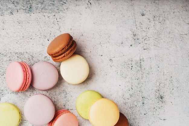Mehrfarbige makkaroni-kekse liegen auf einer grauen steinplatte.