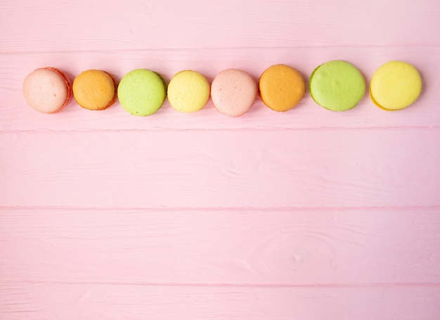 Mehrfarbige makronen auf rosa hintergrund.