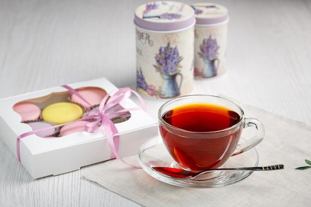 Mehrfarbige makronen in einer schachtel und eine tasse tee auf einem hellen holzküchentisch morgentee und süßigkeiten
