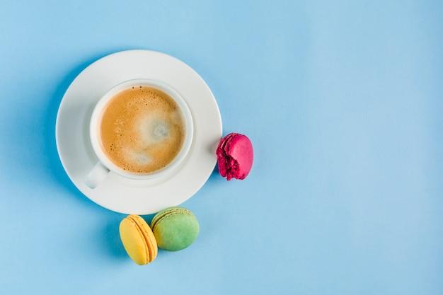Mehrfarbige makronen mit einem weißen tasse kaffee auf einem blauen copyspace, draufsicht, ebenenlage mit copyspace