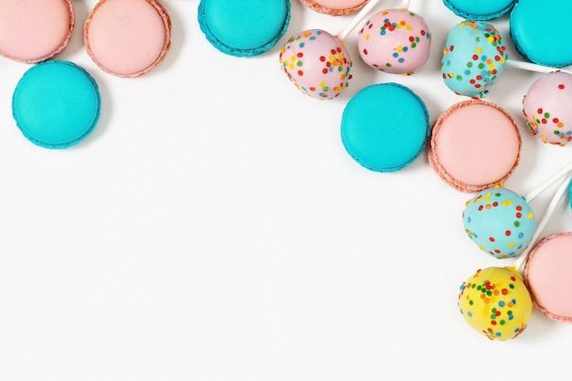 Mehrfarbige makronen und kuchenknalle schließen oben. süßspeise für hintergrund mit kopienraum. verschiedene kekse.