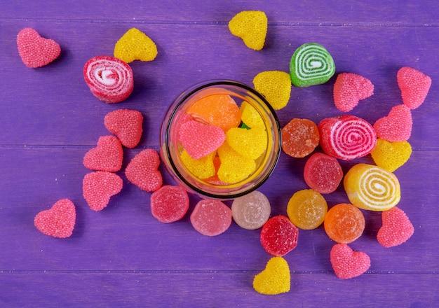 Mehrfarbige marmelade der draufsicht in einem glas auf einem lila hintergrund