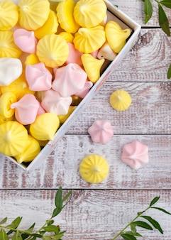 Mehrfarbige meringe in einer geschenkbox auf hölzernem weinlesehintergrund.