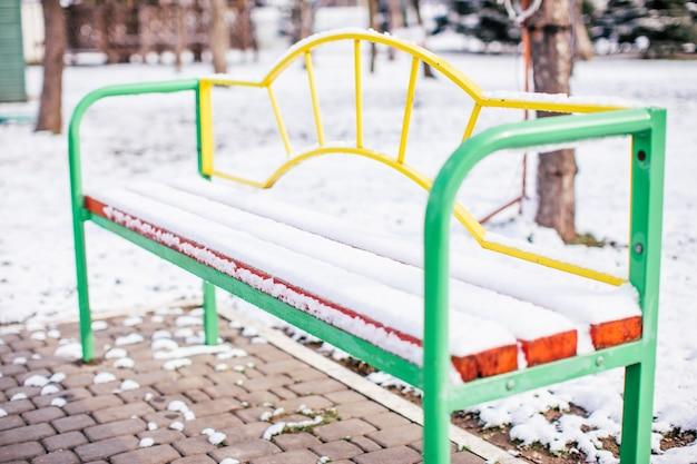 Mehrfarbige metallbank bedeckt mit dem schnee in einem stadtpark.