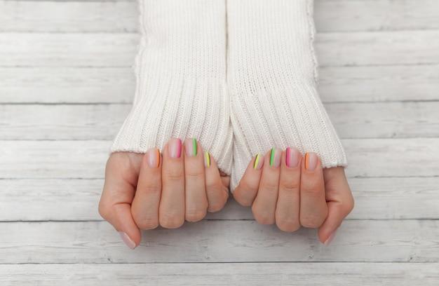Mehrfarbige moderne maniküre, nageldesign, sommerstimmung, hände in einer draufsicht der weißen strickjacke