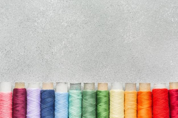 Mehrfarbige nähgarne des regenbogens mit kopienraum