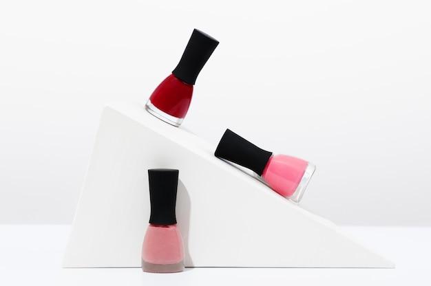 Mehrfarbige nagellacke auf geometrischen formen auf weißem hintergrund. präsentation von beauty-produkten für professionelles make-up und pflege. modische glasflaschen mit flüssigem rosa und rotem lack.