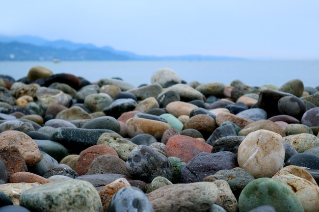 Mehrfarbige natürliche kieselsteine am strand mit seelandschaft