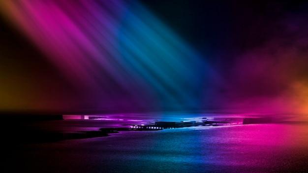 Mehrfarbige neonlichter auf einer dunklen stadtstraßenreflexion von neonlicht in pfützen und wasser abstrakten nachthintergrund
