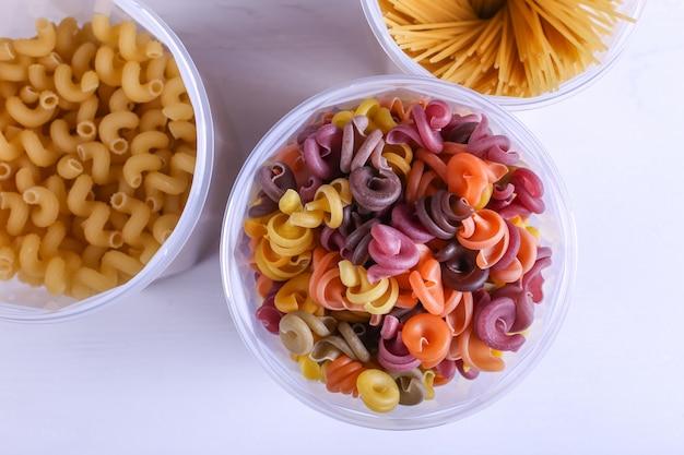 Mehrfarbige nudeln mit zusatz von natürlichem pflanzenfarbstoff. in einem glas auf einem weißen tisch