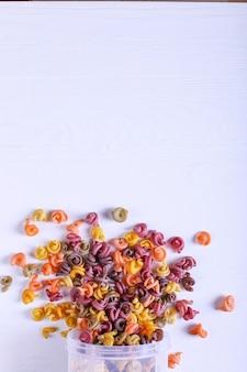 Mehrfarbige nudeln mit zusatz von natürlichem pflanzenfarbstoff. zerstreut von der dose auf dem weißen tisch