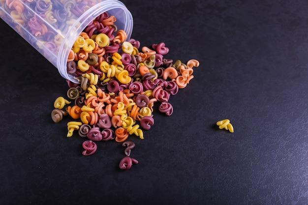 Mehrfarbige nudeln mit zusatz von natürlichem pflanzenfarbstoff. zerstreut von einer dose auf einem schwarzen betontisch