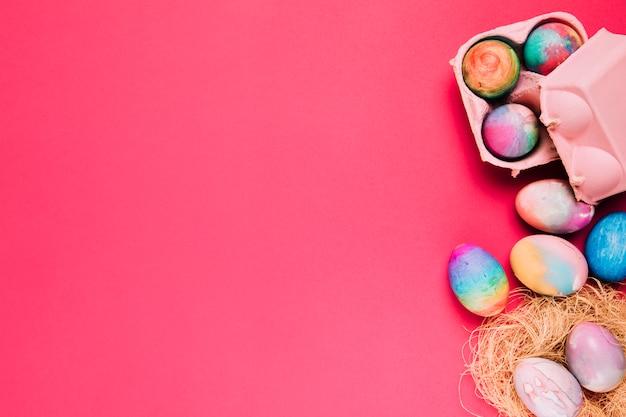 Mehrfarbige ostereier im nest und im kartonkasten auf rosa hintergrund
