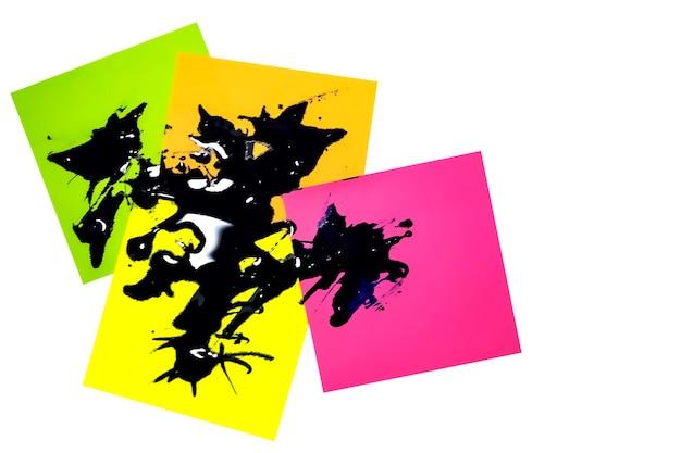 Mehrfarbige papieraufkleber mit farbe übergossen. abstrakte hintergrundnahaufnahme. konzept für unternehmen.