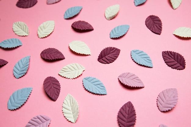 Mehrfarbige papierblütenblätter auf rosa hintergrund
