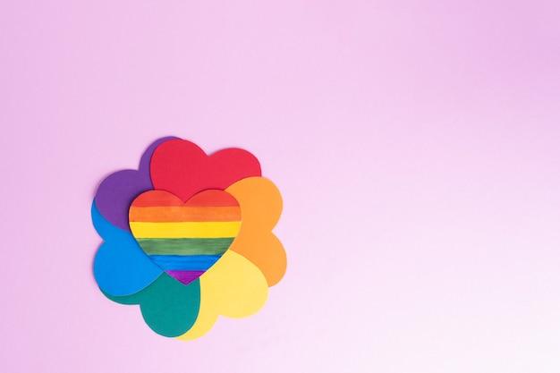 Mehrfarbige papierherzen, die eine blumenform mit regenbogenblättern und einem regenbogenherz in der mitte gegen einen rosa hintergrund bilden, kopieren raum