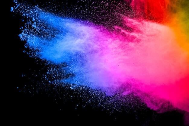 Mehrfarbige partikelexplosion auf weißem hintergrund. bunter staub splatter auf weißem hintergrund.