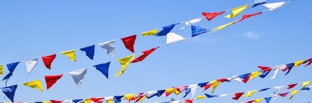Mehrfarbige party-regenbogenfahnen auf blauem himmel zum feiern.