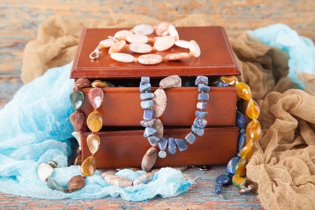 Mehrfarbige perlen und halsketten von halbedelsteinen auf einem alten hölzernen hintergrund. damenschmuck