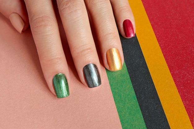 Mehrfarbige perlmutt-maniküre auf kurzen nägeln. nagelkunst. nageldesign rot, grün, grau, beige, goldgelber nagellack.