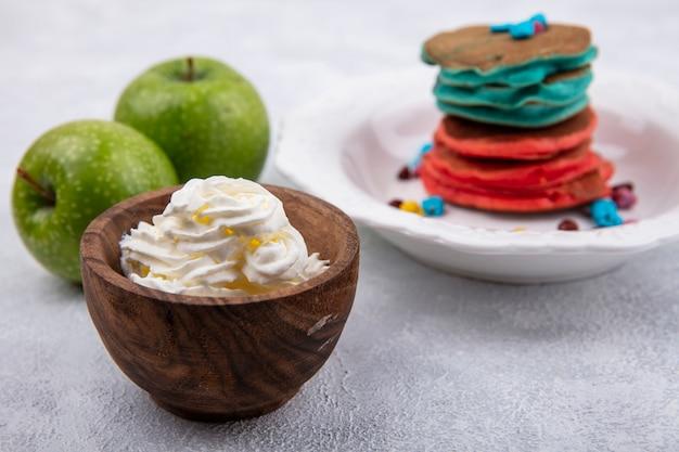 Mehrfarbige pfannkuchen der vorderansicht auf einem stand mit grünen äpfeln und schlagsahne in einer untertasse auf einem weißen hintergrund